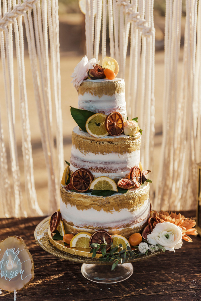 The wedding cake was semi naked, with gold touches, dried and usual citrus slices plus blooms