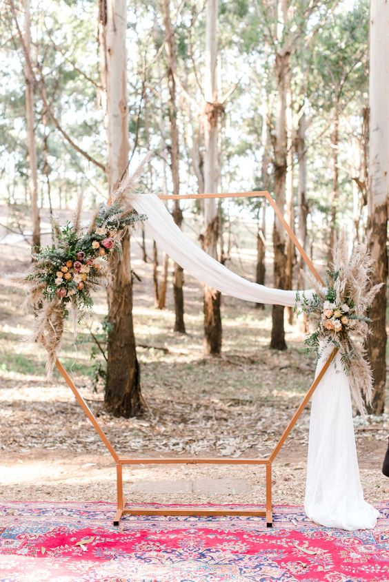 a hexagon wedding arch in copper, with textural greenery, pampas grass, pink and yellow blooms and light fabric
