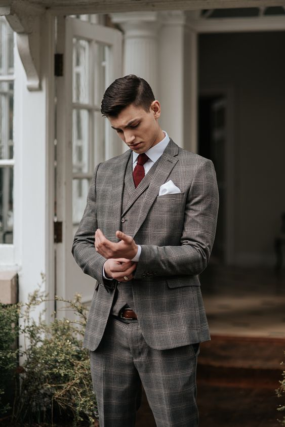 a grey checked three-piece suit, a white shirt, a burgundy bow tie and a brown belt for a touch of vintage