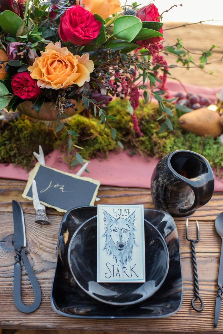 a unique and catchy wedding tablescape with black plates, unusual cutlery, a bright floral centerpiece and a moss runner