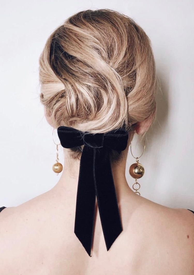 a wavy short hairstyle highlighted with a black velvet ribbon bow and statement mismatching earrings
