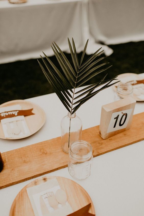 a bottle with a single tropical leaf is an easy and budget-friendly option of a minimalist centerpiece