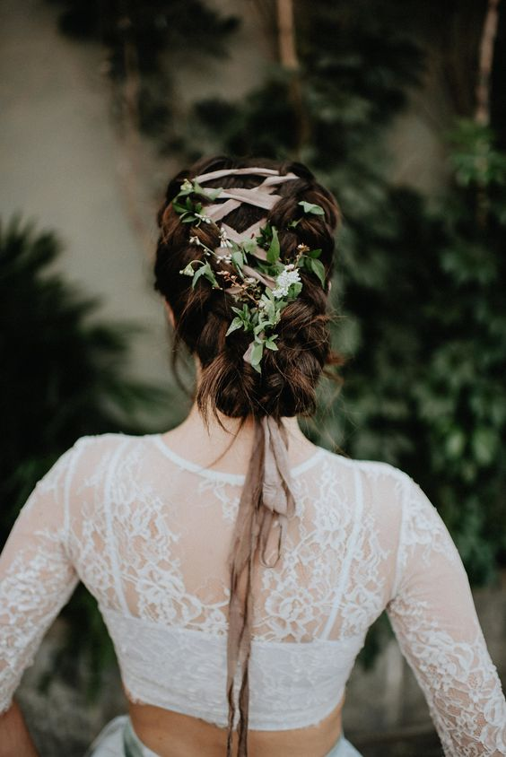 a unique braided low updo with a blush ribbon and fresh greenery interwoven looks very eye-catchy and boho