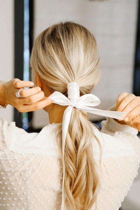 a low ponytail plus a ribbon hair wrap and a bow to highlight your hairstyle and make it catchy