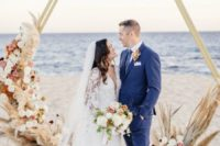 16 a luxurious hexagon wedding arch decorated with blusha nd dusty pink blooms, white flowers and pampas grass for an oceanfrotn ceremony