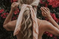 17 a messy wavy low ponytail with a texturla top and a pink scarf instead of a ribbon for an effortlessly chic look