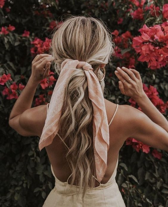 a messy wavy low ponytail with a texturla top and a pink scarf instead of a ribbon for an effortlessly chic look