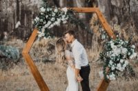 17 a stylish hexagon stained wooden arch decorated with white flowers and greenery looks very cute and trendy