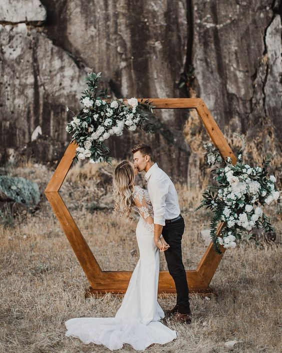 a stylish hexagon stained wooden arch decorated with white flowers and greenery looks very cute and trendy