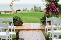18 a tropical hexagon wedding arch decorated with tropical leaves, bright pink florals and tropical fruits at the base