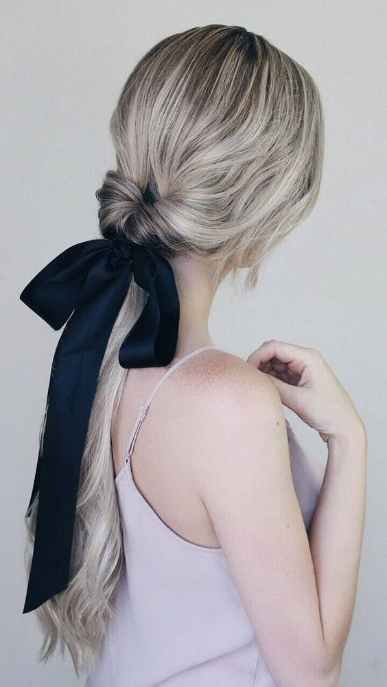 a twisted low ponytail with a sleek top and a black ribbon bow that adds drama to this cute hairstyle