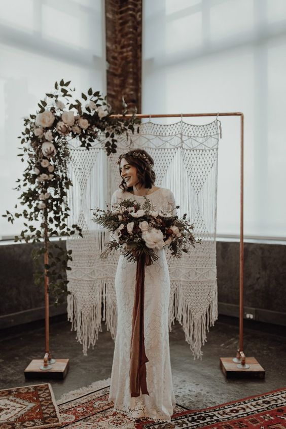 a copper wedding arch with a macrame hanging, some foliage and white blooms on one corner