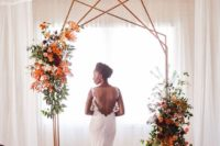 21 a creative polygon wedding arch in copper with lush greenery, fall leaves, blooms and rugs for a fall wedding