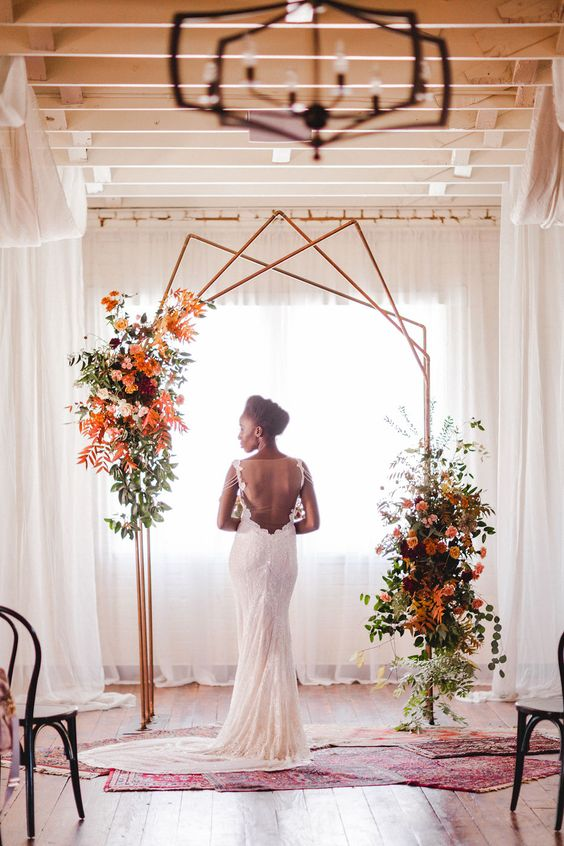a creative polygon wedding arch in copper with lush greenery, fall leaves, blooms and rugs for a fall wedding