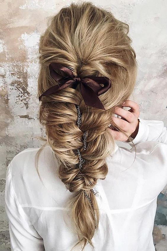 a dimensional fishtail braid with a bump and a brown ribbon bow plus a chain to accent the hairstyle