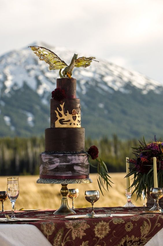 a cool GOTH wedding cake with matte and watercolor tiers, burgundy blooms and a dragon topper