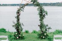 23 a polygon copper arch with lush greenery decor and blush blooms for a summer wedding