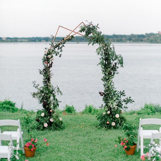 a polygon copper arch with lush greenery decor and blush blooms for a summer wedding