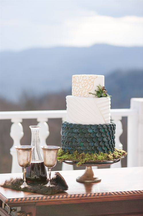 a gorgeous GOTH wedding cake with a gold crack, textural and green scale tier plus greenery and moss