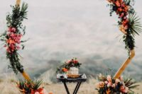 24 a polygon wedding arch decorated with greenery and tropical leaves, bright orange and pink blooms and tropical fruits