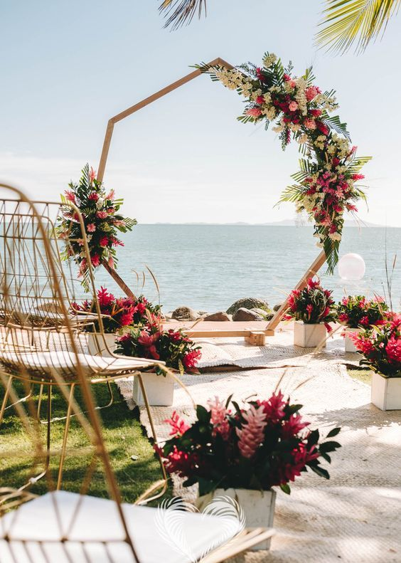a super bright polygon wedding arch decorated with yellow, hot pink and fuchsia blooms and the same arrangements in pots