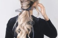 26 a gorgeous low chignon going into a long wavy pinytail and a sheer and etherel grey ribbon with a bow