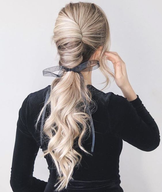 a gorgeous low chignon going into a long wavy pinytail and a sheer and etherel grey ribbon with a bow