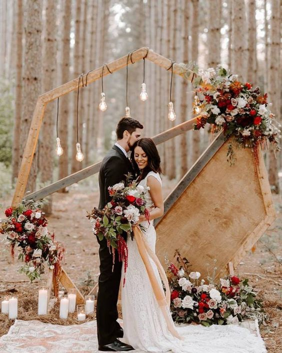 a unique polygon wedding arch with a plywood part, lush floral and greenery decor in red and pink, bulbs and multiple candles