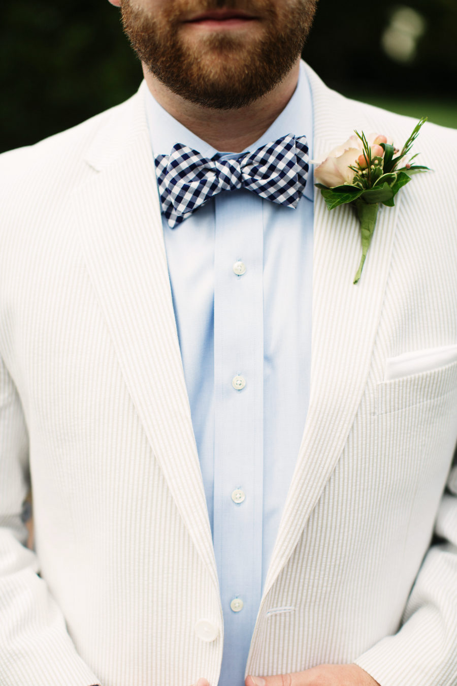 a neutral thin stripe suit with a blue shirt and a checked bow tie for a fresh spring or summer look
