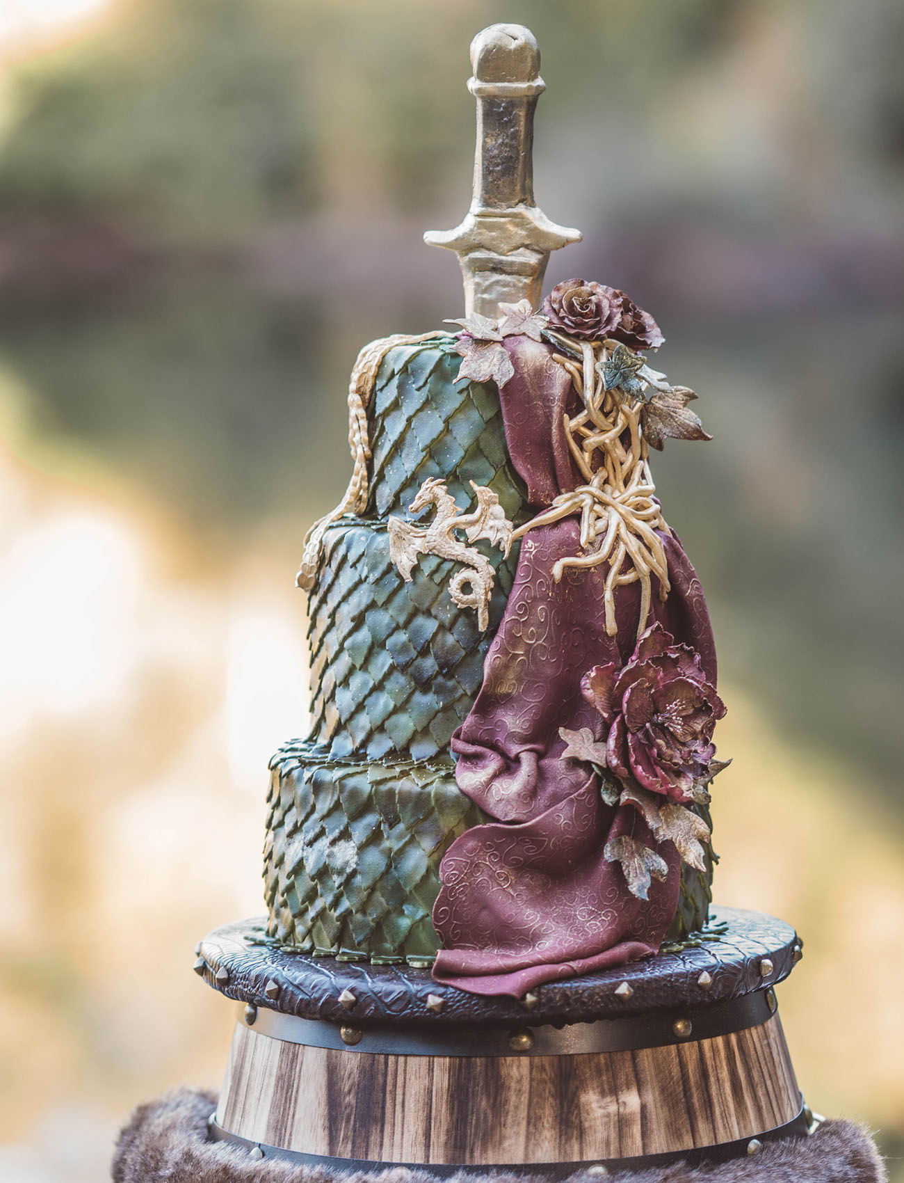 a unique wedding cake imitating green dragon scale, gilded dragons, a sword, sugar blooms looks very GOTH like