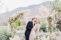 27 an asymmetrical geometric wedding arch decorated with pampas grass, neutral and dusty pink blooms and greenery