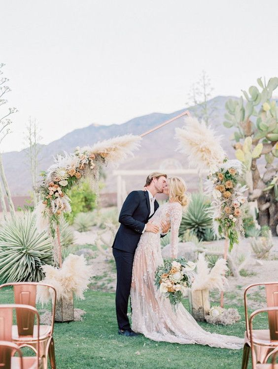 an asymmetrical geometric wedding arch decorated with pampas grass, neutral and dusty pink blooms and greenery