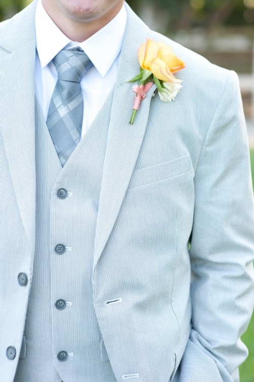 a refreshing groom outfit with a light blue thin stripe three-piece suit, a white shirt and a printed tie plus a yellow boutonniere