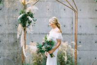28 an industrial polygon copper wedding arch decorated with greneery and pampas grass plus the same decor on the ground