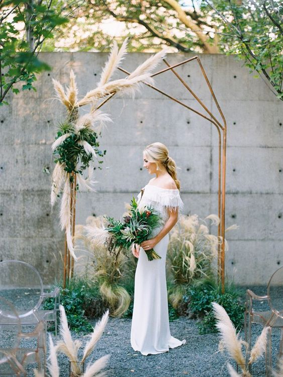 an industrial polygon copper wedding arch decorated with greneery and pampas grass plus the same decor on the ground