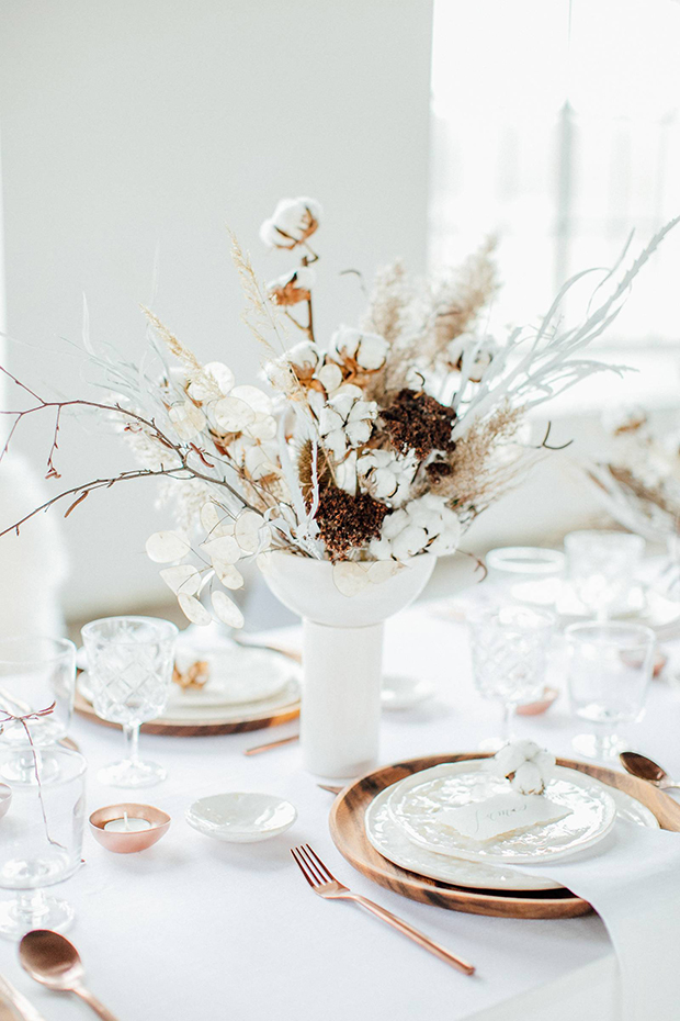 a beautiful wedding centerpiece of cotton branches, lunaria, branches and some dried berry branches is very delicate and chic