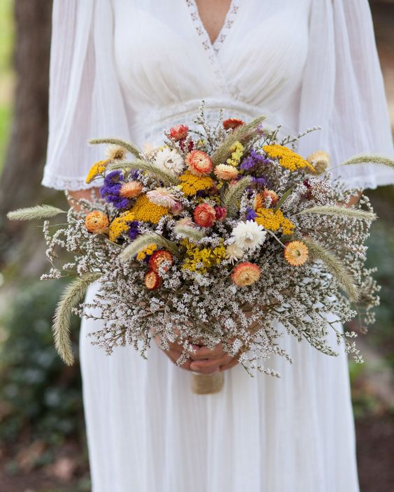 a bright wedding bouquet with white fresh blooms, dried yellow, purple and rust flowers and dried wheat