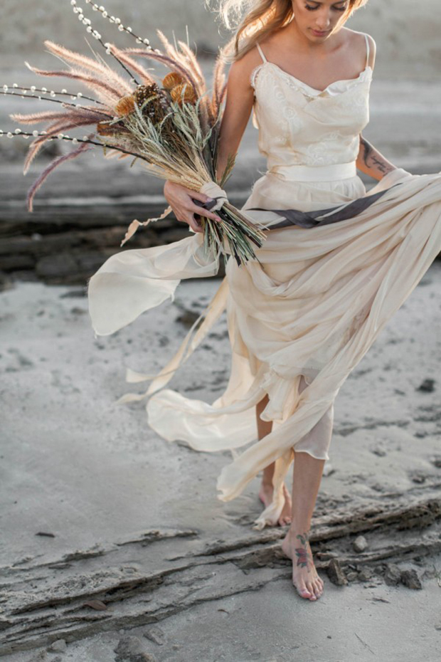 a catchy and textural bridal bouquet of dried flowers, grasses and branches and is a unique idea for a boho bride