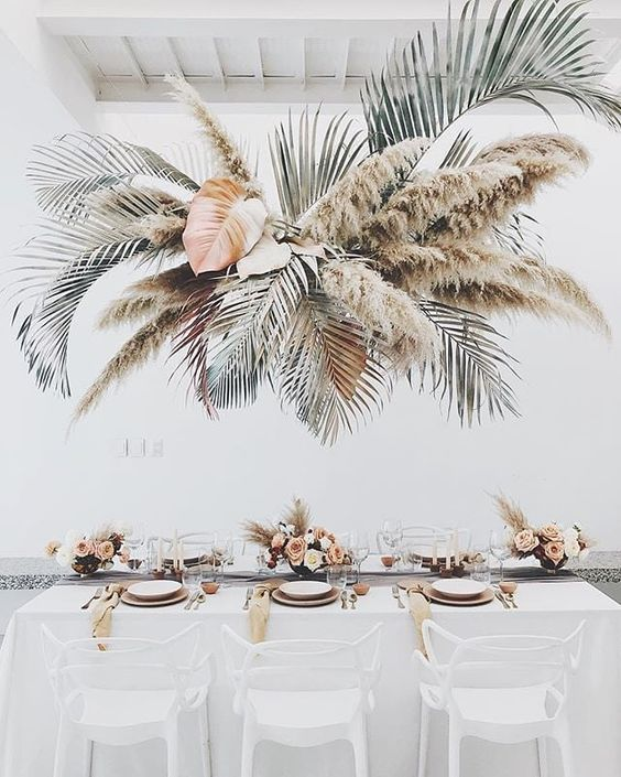 a chic overhead arrangement of dried fronds, leaves and pampas grass for a boho tropical wedding
