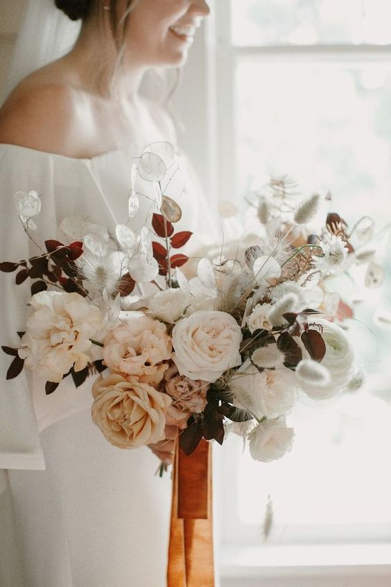 a delicate and soft wedding bouquet featuring dried lunaria, grasses and garden roses, leaves and rust-colored ribbons