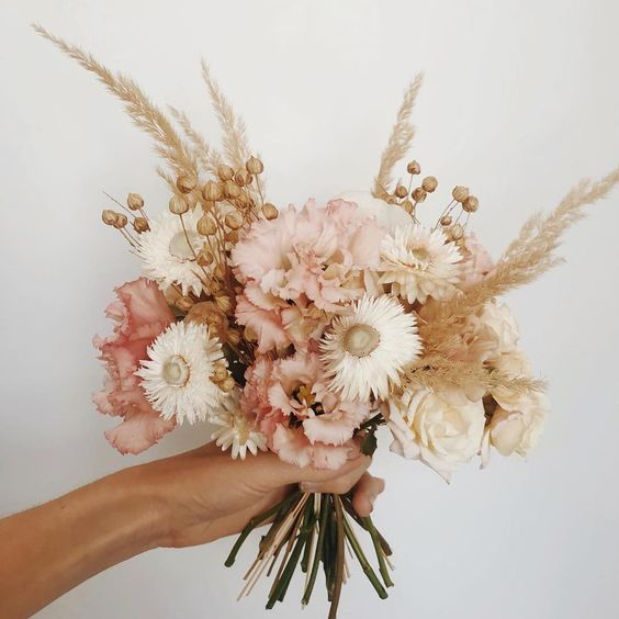 a delicate and subtle wedding bouquet of white and blush blooms, seed pods and wheat is a very romantic idea