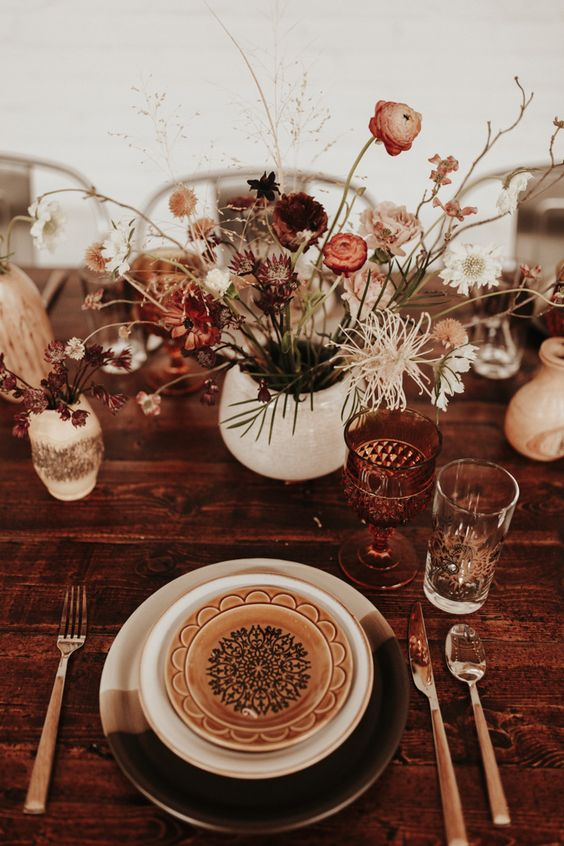 a dried flower fall wedding centerpiece of blooms and herbs, with foliage and branches is a chic boho decoration