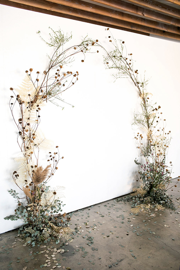 a fantastic wedding ceremony arch of eucalyptus, dried leaves and herbs plus dried billy balls looks ethereal and delicate