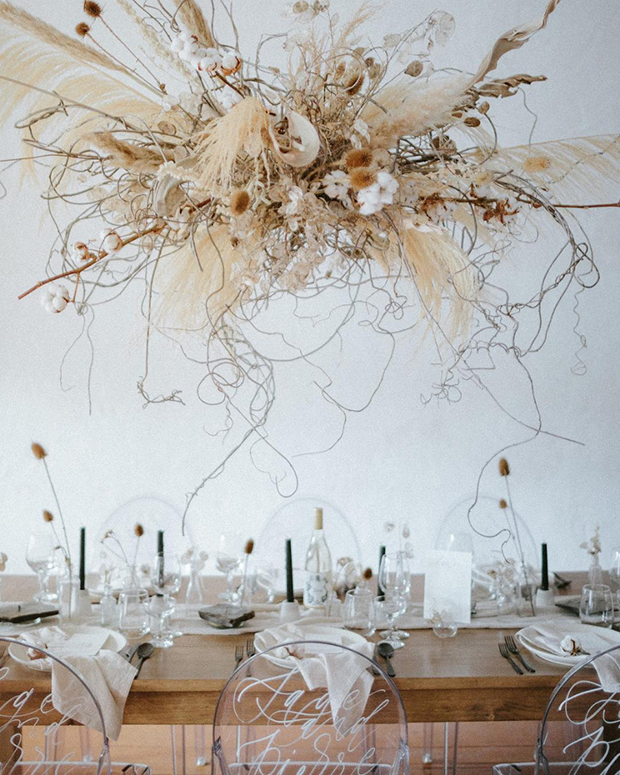 a gorgeous overhead arrangement of cotton branches, pampas grass, seed pods, dried blooms and herbs