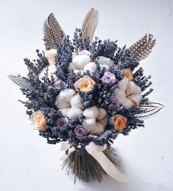 a lovely wedding bouquet with lavender, peachy and lilac roses, cotton and feathers is a creative idea