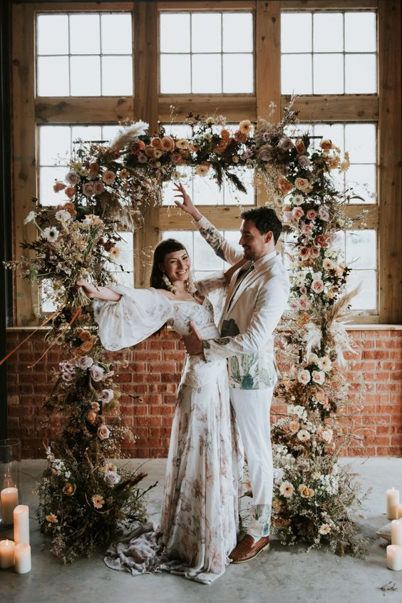 a moody wedding arch composed of dried blooms and foliage, white, blush and burgundy fresh flowers