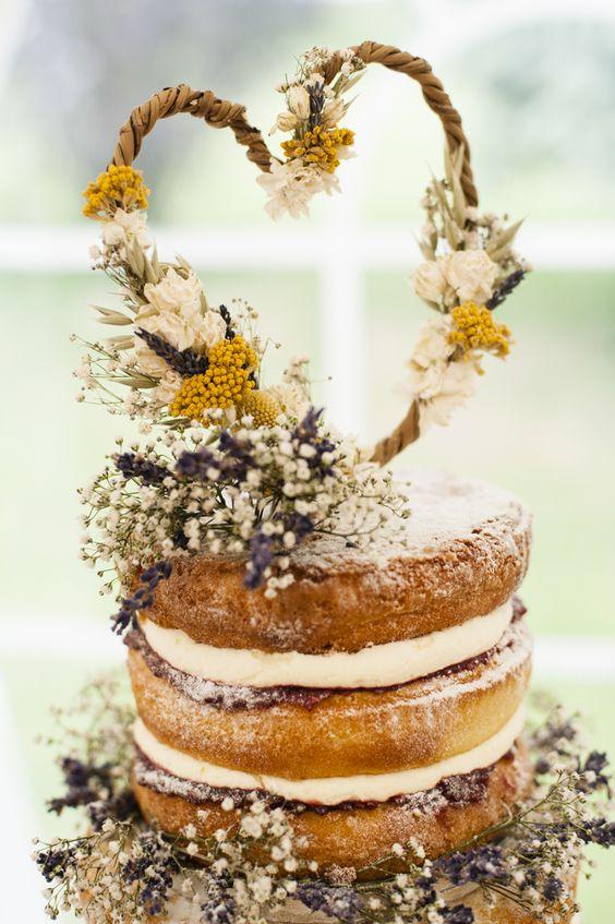 a naked wedding cake decorated with dried flowers, leaves and fresh blooms in yellow and white for a rustic wedding