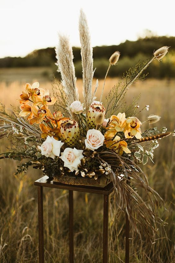 a sculptural boho wedding centerpiece with yellow orchids, ivory roses, dried foliage and pampas grass in earthy tones