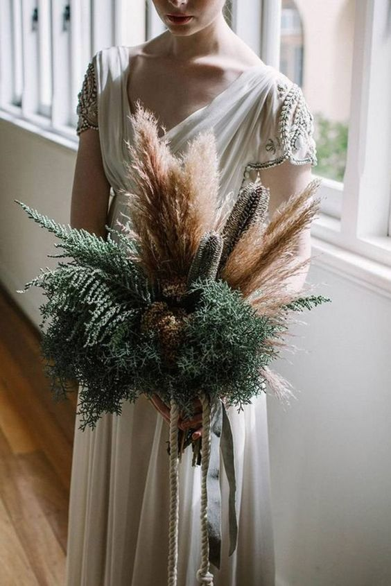 a stylish wedding bouquet done of wheat, pampas grass, ferns and dried blooms features much texture