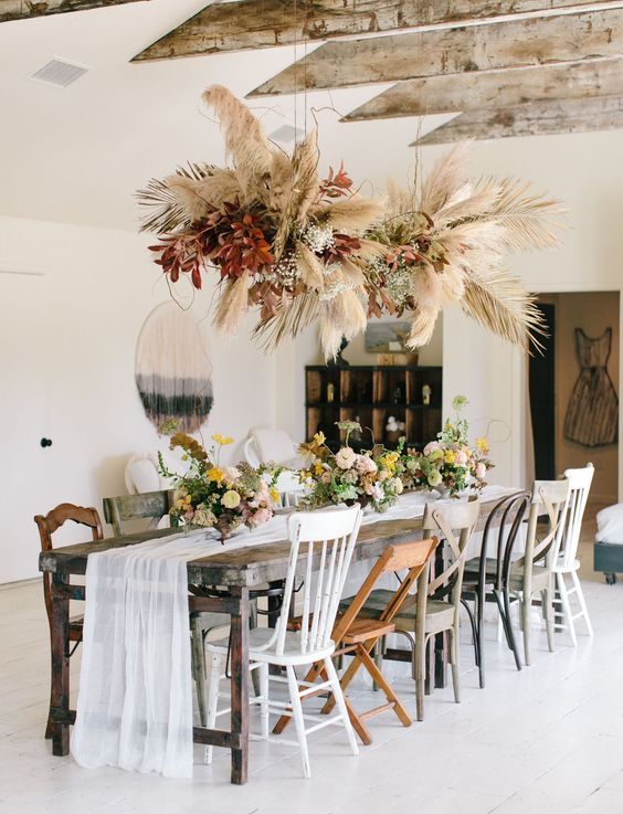 an overhead floating arrangement of pampas grass, dried leaves and fronds plus bright burgundy foliage